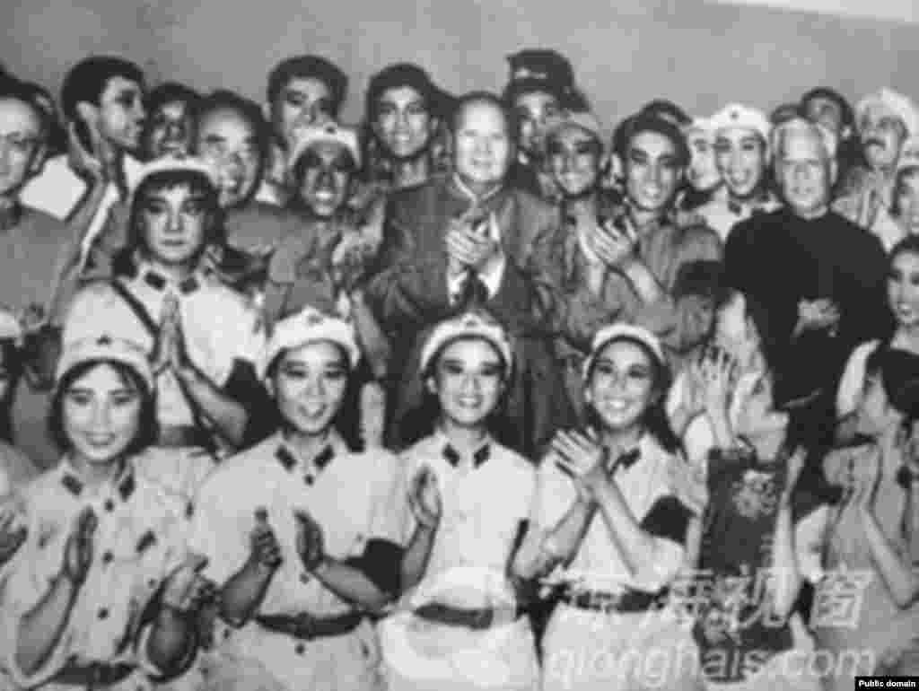 """1964年10月8日,毛泽东、刘少奇、朱德、康生(左侧戴眼镜者)等中国领导人观看芭蕾舞剧《红色娘子军》,并与演员合影。后来的文革中,有大字报批判主要演员白淑湘说,毛主席和刘少奇接见演员时,别人喊毛主席万岁,而白淑湘喊刘主席万岁。康生是毛泽东的亲信和打手,在共产党内一直担任颇具神秘色彩的保卫、情报等部门的领导工作,被比作中国的捷尔任斯基、贝利亚。他1980年被中共开除党籍,被法庭认定為""""林彪、江青反革命集团案主犯""""。"""