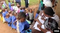 FILE - Schoolchildren line up for trachoma medicine in Buniantole, eastern Uganda, Sept. 12, 2012. (Hilary Heuler/VOA)