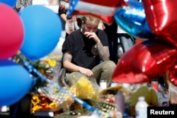 Bry Thompson wipes away tears at a makeshift memorial in the middle of Las Vegas Boulevard following the mass shooting in Las Vegas, Nevada, Oct. 4, 2017.