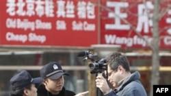 Cảnh sát Trung Quốc yêu cầu một phóng viên của AP rời khỏi 1 khu vực gần khu mua sắm Wangfujing ở Bắc Kinh, Chủ Nhật 27/2/2011