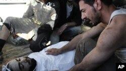 14일 시리아 정부군의 홈스시 폭격으로 사망한 희생자의 사체와 오열하는 남성.