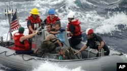 지난 6일 미 해군 경비경들이 태평양 한 가운데서 조난당한 가족을 구조하고 있다.