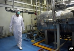 FILE - An Iranian technician walks through a uranium conversion facility just outside Isfahan, south of the capital, Tehran, in this February 2007 photo.