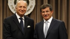 Turkish Foreign Minister Ahmet Davutoglu (R) and his French counterpart Laurent Fabius shake hands after a news conference in Ankara August 17, 2012.
