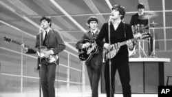 The Beatles are seen performing, date unknown. From left to right: Paul McCartney, George Harrison, John Lennon, and Ringo Starr on drums.