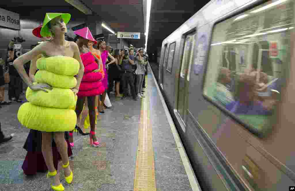 Models wearing collections of previous editions of the Sao Paulo Fashion Week, stand inside a subway station in Sao Paulo, Brazil, Oct. 27, 2013.