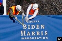 """工作人员在白宫前的宾夕法尼亚大道上的就职典礼媒体观礼台安装有""""2021拜登哈里斯""""字样的横幅。(2021年1月14日)"""