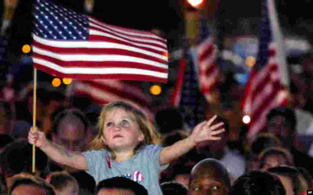 Four-year-old Alana Milawski waves an American flag as she sits on her father Craig Milawksi's shoulders during a candlelight vigil, held to honor those killed in terrorist attacks in New York and Washington, in Las Vegas.
