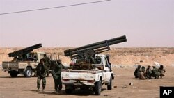 Libyan rebels gather around armed vehicles at Ajdabiya's western gate after rebels re-controlled the area, on April 17, 2011