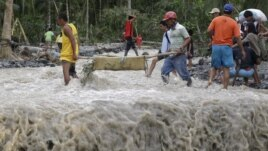 Residents cross a river with the body of a child after retrieving it from the flash flood-hit village of Andap, in New Bataan township, Compostela Valley in southern Philippines, December 5, 2012.