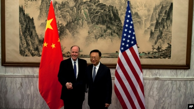 U.S. National Security Adviser Tom Donilon, left, and Chinese State Councilor Yang Jiechi, right, shake hands before their meeting at Diaoyutai State Guesthouse in Beijing, May 27, 2013.