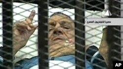Photo d'archives: L'ancien président égyptien Hosni Moubarak gesticule dans la salle d'audience lors de son procès à l'académie de police au Caire, le 15 août, 2011.