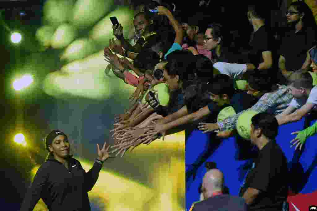 US tennis player Serena Williams (L) of the Singapore Slammers enters the court during the International Premier Tennis League (IPTL) competition in Singapore.
