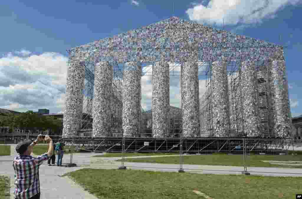 បុរសម្នាក់ថតរូបផ្ទាំងសិល្បៈ The Parthenon of Books ដែលរចនាឡើងដោយសិល្បករ Marta Minujin របស់អាហ្សង់ទីន។ សំណង់នេះកំពុងត្រូវបានសាងសង់សម្រាប់ការតាំងពិព័រណ៍សិល្បៈ ក្នុងក្រុង Kassel ប្រទេសអាល្លឺម៉ង់។