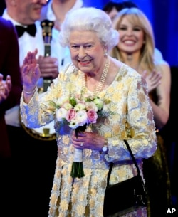 Queen Elizabeth II waves from the stage at the Royal Albert Hall in London, April 21, 2018, for a concert to celebrate her 92nd birthday.