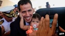 Pemimpin oposisi Venezuela yang memproklamirkan dirinya sebagai presiden sementara, Juan Guaido (tengah) berpose degan seorang bayi sebelum meninggalkan hotel di Salinas, Ekuador, 3 Maret 2019 (foto: Rodrigo Buendia/AFP)