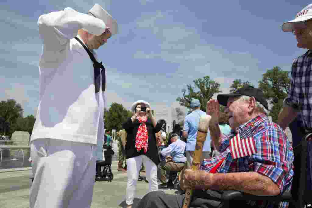Navy Petty Officer Kevin Smith, left, salutes WWII veteran Harold Noel, 98, who was a B-24 navigator during WWII and was shot down and imprisoned as a POW at Stalag Luft III, at the World War II Memorial in Washington D.C. during a ceremony in honor of the 70th anniversary of Victory in Europe Day (VE Day), May 8, 2015,