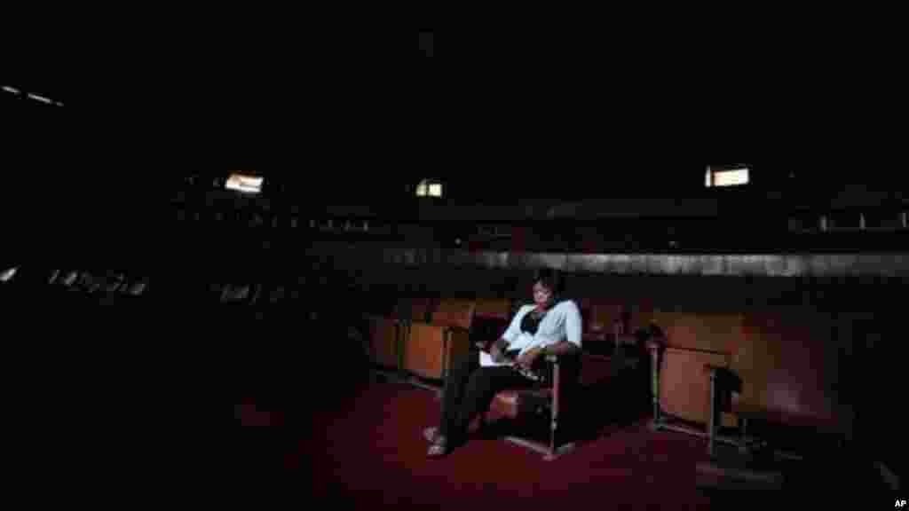 A worker sits in the abandoned bowl theater of Nigeria's National Theatre in Lagos, Nigeria.