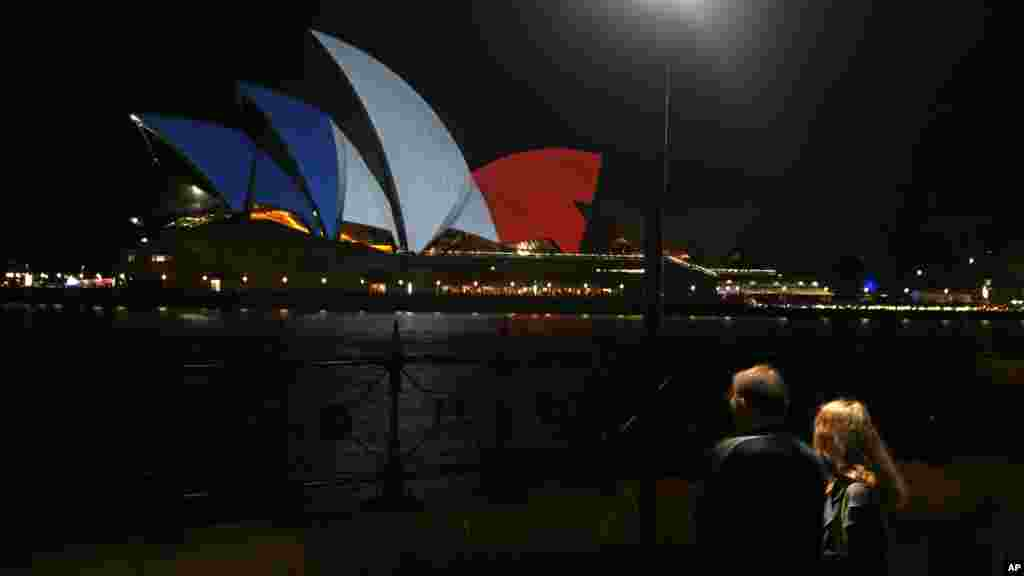 A couple look at the sails of the Sydney Opera House that are lit in the colors of the French flag in Sydney, following the terrorist attacks in Paris, Nov. 14, 2015.