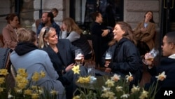 FILE - In this Wednesday, April 8, 2020 file photo people chat and drink outside a bar in Stockholm, Sweden. Sweden is pursuing relatively liberal policies to fight the coronavirus pandemic, even though there has been a sharp spike in deaths. (AP Photo/An