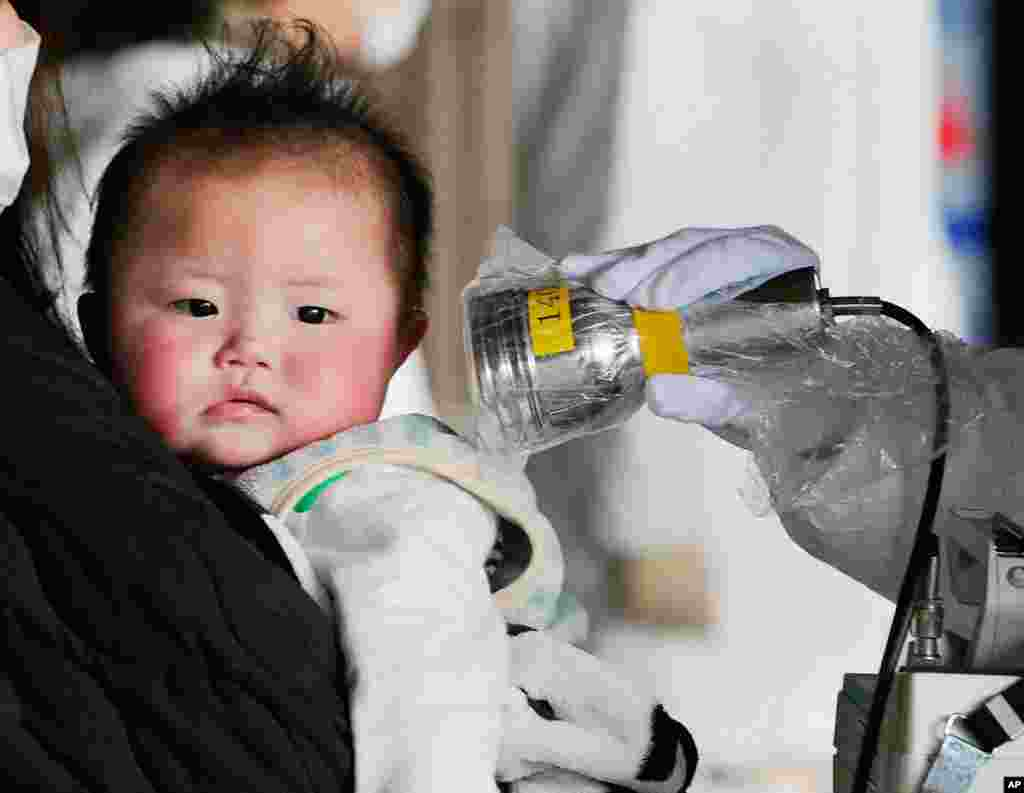 Tokyo residents were warned not to give babies tap water because of radiation leaking from a nuclear plant crippled in the earthquake and tsunami. Here a baby is checked for radiation in Fukushima City on March 24, 2011. (Reuters/Kyodo)