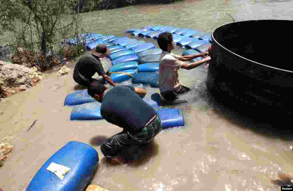 A group of men smuggle diesel fuel from Syria to Turkey hoping to sell it at a higher price, across the Al-Assi River in Idlib, May 26, 2013.
