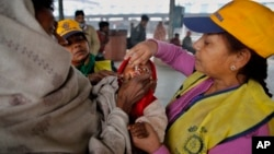 A medical volunteer administers polio immunization drops to a child at a railway station in Allahabad, India, Jan. 13, 2014.