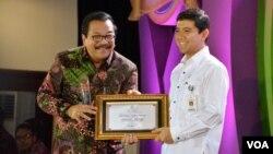 MenPan RB Yuddy Chrisnandi (kanan) memberikan penghargaan Layanan Publik kepada Gubernur Jawa Timur Soekarwo di Surabaya hari Kamis 31/3 (VOA/Petrus). Yuddy di Surabaya mengatakan bahwa dirinya sama sekali tidak mengetahui keberadaan surat permintaan fasilitas itu.