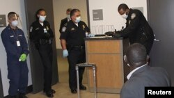 U.S. Customs and Border Protection officers perform enhanced passenger screening of an international traveler, who recently visited Guinea, at Atlanta's International Airport Oct. 16, 2014.
