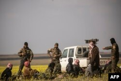 FILE - Men suspected of being Islamic State fighters arrive at a screening point run by U.S.-backed Syrian Democratic Forces, where suspected jihadists were being interrogated outside Baghuz in Syria, March 6, 2019.