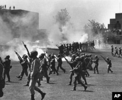 FILE - Ohio National Guard moves in on rioting students at Kent State University in Kent, Ohio, May 4, 1970. Four persons were killed and 11 wounded when National Guardsmen opened fire.