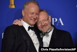 """Stellan Skarsgard, left, and Jared Harris, from the cast of """"Chernobyl,"""" winners of the award for best television limited series or motion picture made for television, pose in the press room at the 77th annual Golden Globe Awards."""
