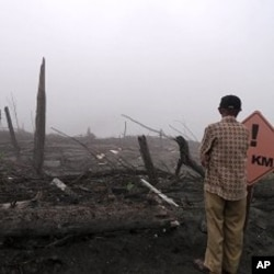A tourist takes in the destruction wrought by weeks of violent eruptions, in Kaliurang in Central Java, 11 Jan 2011.