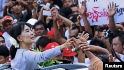 Burma's pro-democracy leader Aung San Suu Kyi touches the hands of her supporters as she arrives to attend the opening ceremony of her National League for Democracy (NLD) party's branch office in Yangon, May 23, 2012.