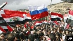 Những người ủng hộ Tổng thống Syria cầm cờ Syria và cờ Nga tham gia một cuộc mít tinh tại quảng trường Umayyad ở Damascus hôm 15/3/12