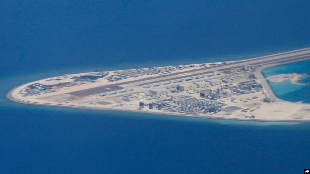菲律宾空军一架运输机在南中国海南沙群岛的中国造的人造岛礁渚碧礁上空飞越时拍摄的照片,显示人造岛礁上的简易机场和建筑物。(2017年4月21日)