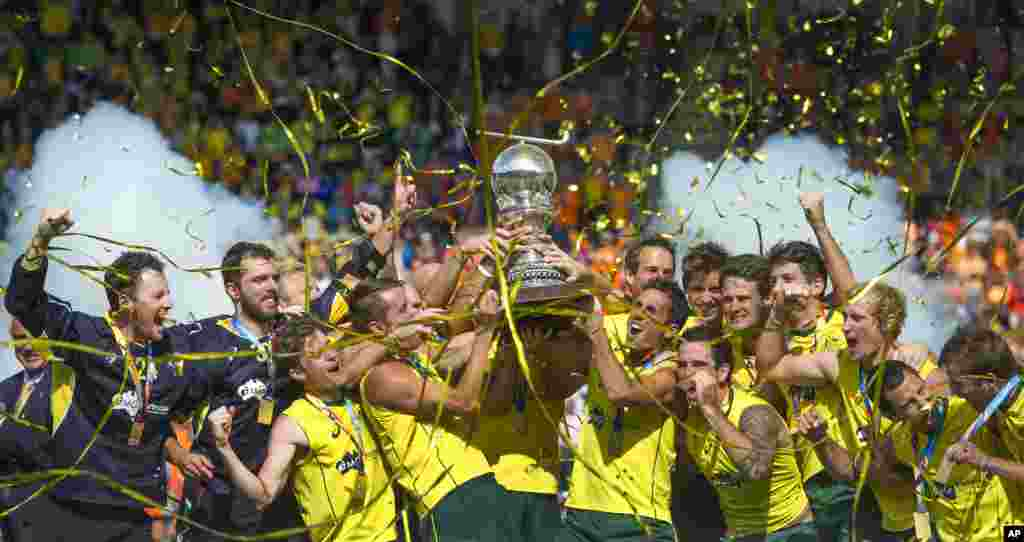 Australian players celebrate holding the trophy after winning the men's final of the Field Hockey World Cup between Australia and The Netherlands in The Hague, Netherlands. Australia beat the Netherlands with a 6-1 score.