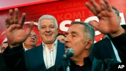 FILE - Montenegro's Prime Minister and long-ruling Democratic Party of Socialists leader Milo Djukanovic, front, speaks in his headquarters while his deputy, Dusko Markovic, stands behind him in Podgorica, Montenegro, Oct. 17, 2016.