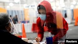 Seorang pemilih muda mengisi surat suara dibantu oleh petugas pemungutan suara di tempat pemungutan suara di mal Midtown Center, Milwaukee, pada hari pertama pencoblosan langsung, di Wisconsin, 20 Oktober 2020. (Foto: Reuters)