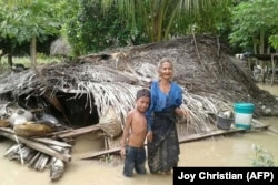 Une vielle femme et son petit-fils se tiennent devant leur maison endommagée dans le village de Haitimuk, dans l'est de Flores, le 4 avril 2021.