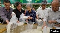 资料照:山西省太原市一家超市里的顾客在买大米。(2013年5月22日)