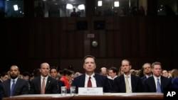 Cựu giám đốc FBI James Comey nghe Chủ tịch Ủy ban Tình báo Thượng viện phát biểu vào đầu phiên điều trần trong Quốc hội, ngày 8 tháng 6, 2017, ở Washington.