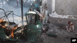 People are seen at the site of bombing in Quetta, Pakistan, September 7, 2011.