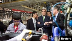 U.S. Secretary of State John Kerry (C) takes a tour of the Foton Cummins Engine plant in Beijing, Feb. 15, 2014.