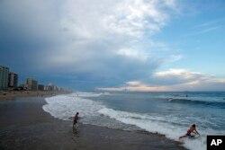 Surfers aprovechan las olas en Virginia Beach, Virginia, el 11 de septiembre de 2018, antes de la llegada del huracán Florence.