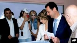 Tổng thống Syria Bashar al-Assad (thứ hai từ phải sang) cùng phu nhân đi bầu tại một điểm bỏ phiếu ở Damascus, 3/6/2014.