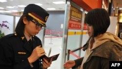 Nhân viên an ninh sân bay kiểm tra hộ chiếu và thẻ lên máy bay của một hành khách tại phi trường Taipei Songshan, ngày 10/3/2014.