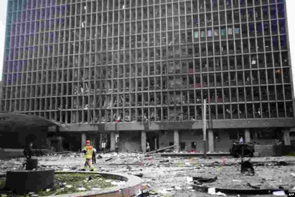 Debris covers the area outside a building in the centre of Oslo, Friday July 22, 2011, following an explosion that tore open several buildings including the prime minister's office, shattering windows and covering the street with documents. (AP Photo/Fart