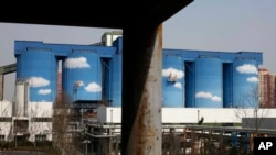 FILE - A commercial plant painted with scenes of clouds and blue skies is seen amid a residential area of Beijing, China.