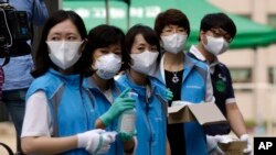 South Korean health workers from a community health center wearing masks as a precaution against MERS, Middle East Respiratory Syndrome, virus, wait to check examinees' temperature and to sanitzie their hands at a test site for a civil service examination